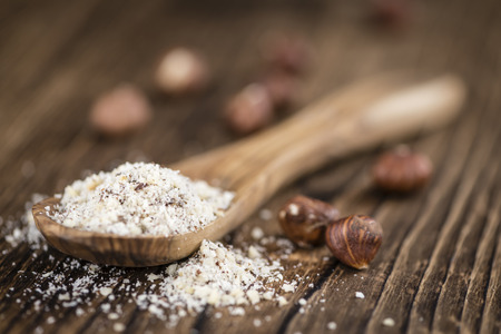 grounded: Wooden table with grounded Hazelnuts (close-up shot; selective focus) Stock Photo