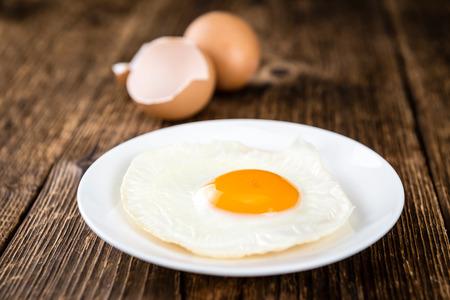 huevos estrellados: Breakfast (fried eggs) on an old wooden table (selective focus; close-up shot) Foto de archivo