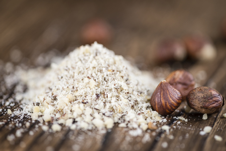 cutted: Grounded Hazelnuts (selective focus; close-up shot) on vintage background