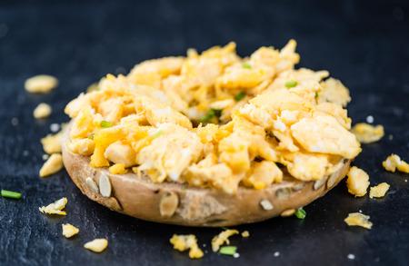 huevos revueltos: Fresh made Bagel with Scrambled Eggs (selective focus; close-up shot)