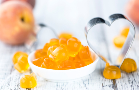 Heap of gummy Peaches on wooden background (close-up shot)