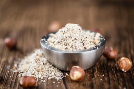 grounded: Hazelnuts (grounded) on vintage wooden background (selective focus; close-up shot)