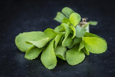 steviol: Portion of Stevia leaves (selective focus; detailed close-up shot) on vintage background