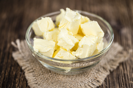 butterfat: Piece of Butter on wooden background (selective focus; close-up shot)