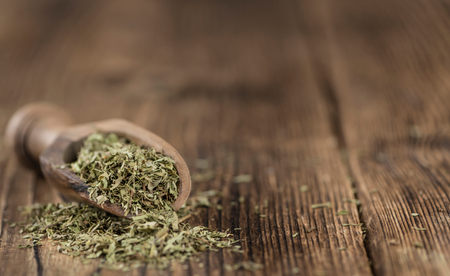 steviol: Old wooden table with dried Stevia leaves (close-up shot; selective focus)