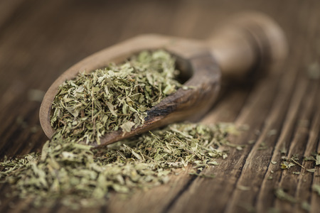 sweetening: Heap of dried Stevia leaves (sweetener) on vintage background (close-up shot) Stock Photo