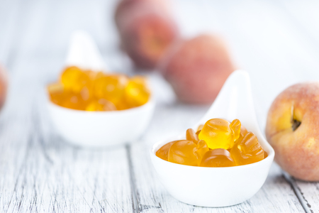 jello: Gummy Peaches (close-up shot) with some fresh fruits on wooden background Stock Photo
