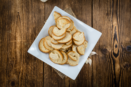 Portion of crunchy bread chips (selective focus; close-up shot) on vintage background