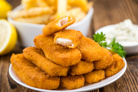 Fried Fish Fingers (selective focus) on wooden background (selective focus)