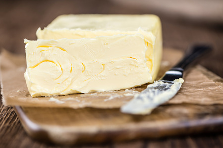 Old wooden table with a portion of Butter (selective focus; close-up shot)) Stock Photo