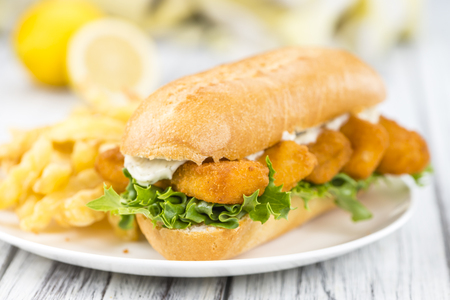 Fresh made Snack (Sandwich with Fish Sticks) on an old wooden table Stock Photo