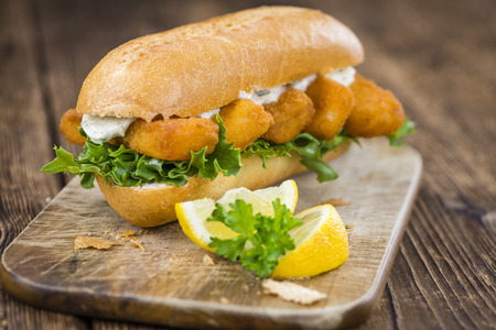 fishfinger: Roll with fried Fish Sticks (close-up shot) on an old wooden table