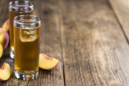 Peach ice tea (selective focus) on an old wooden table (close-up shot) Stock Photo