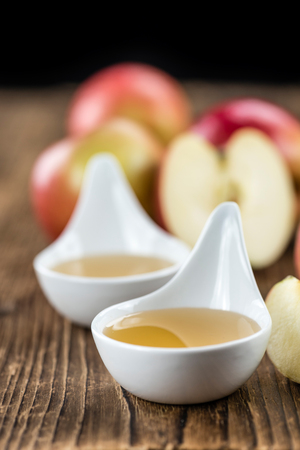 Portion of fresh made Applesauce (selective focus) on wooden background