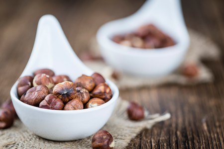 nutshells: Hazelnut Kernels (selective focus; close-up shot) on vintage looking background