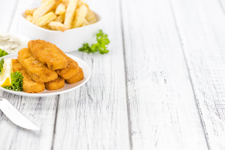 fishfinger: Some fried Fish Sticks (selective focus) on an old wooden table