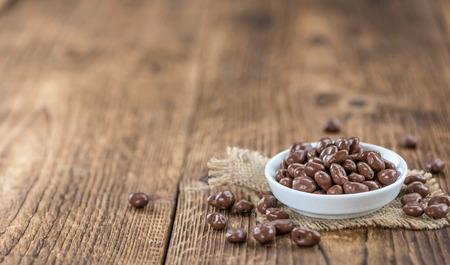 snacking: Old wooden table with Chocolate Raisins (close-up shot) Stock Photo
