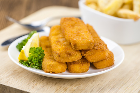 fishfinger: Fisch Sticks (close-up shot) on an old wooden table (selective focus)