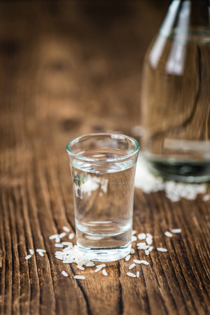 sake: Glass with Sake (selective focus) on an old wooden table Foto de archivo