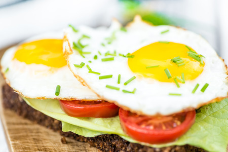 huevos estrellados: Emparedado recién hecho con huevos fritos (cerca de disparo, enfoque selectivo)