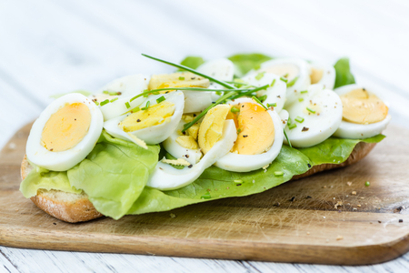 Portion of sliced Eggs (on wooden background) as close-up shot (selective focus)