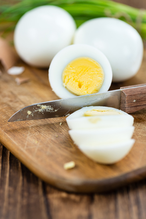 boiled eggs: Portion of boiled Eggs (sliced) on vintage looking background (selective focus) Stock Photo