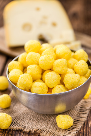 Cheese Balls (fried) as high detailed close-up shot on a vintage wooden table (selective focus) Stock Photo