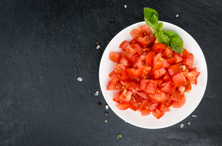 Diced Tomatoes on a vintage background as detailed close-up shot (selective focus)