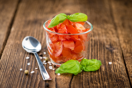 cutted: Homemade Cutted Tomatoes on vintage background (selective focus; close-up shot) Stock Photo