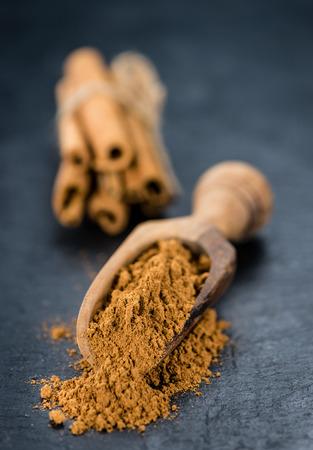 christmas grounds: Portion of Cinnamon Powder on a rustic slate slab (selective focus; close-up shot)