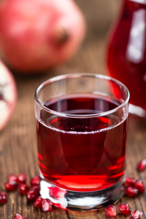 pomegranat: Pomegranate juice as high detailed close-up shot on a vintage wooden table (selective focus) Stock Photo