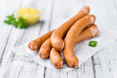 Sausages (Frankfurter) on rustic wooden background (close-up shot)