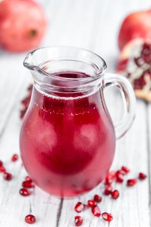 pomegranat: Pomegranate juice on a vintage background as detailed close-up shot (selective focus)