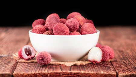 Lychees on a vintage background as detailed close-up shot (selective focus)