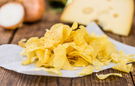 Cheese and Onion Potato Chips on rustic wooden background (close-up shot)