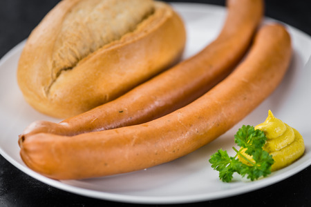 weenie: Sausages (Frankfurter) on a vintage slate slab (close-up shot; selective focus)