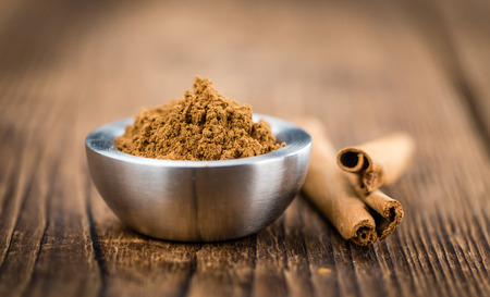 christmas grounds: Cinnamon Powder as high detailed close-up shot on a vintage wooden table (selective focus)