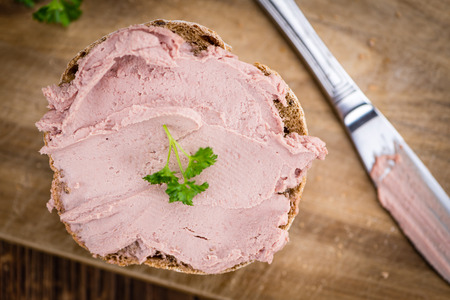 Roll with Liverwurst (German cuisine) on an old wooden table as detailed close-up shot (selective focus)