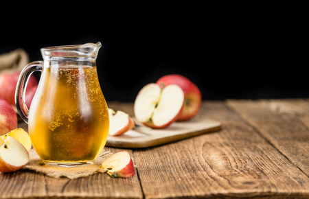 detailed shot: Apple Cider on an old wooden table as detailed close-up shot (selective focus)