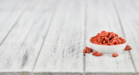 Fresh made Dried Goji Berries on a vintage background (close-up shot)