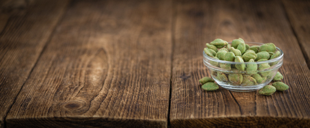 detailed shot: Wasabi coated Peanuts as high detailed close-up shot on a vintage wooden table (selective focus)