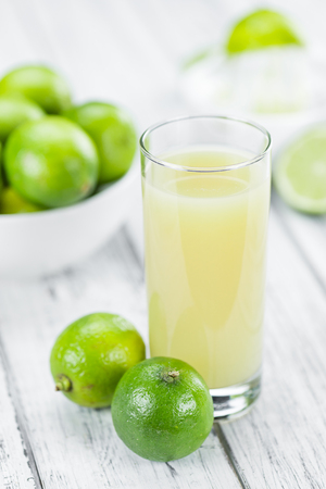 Fresh Lime Juice as high detailed close-up shot on a vintage wooden table (selective focus) Stock Photo