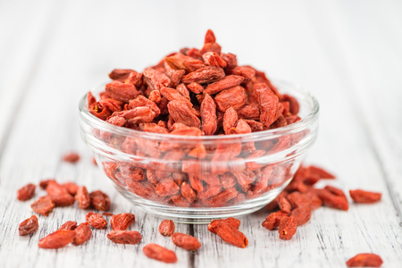detailed shot: Goji Berries (dried) on an old wooden table as detailed close-up shot (selective focus)