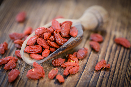 chinese wolfberry: Dried Goji Berries as high detailed close-up shot on a vintage wooden table (selective focus)