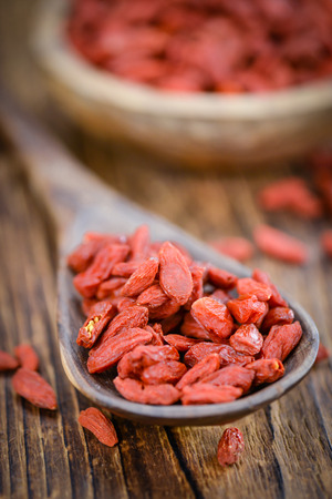 detailed shot: Dried Goji Berries as high detailed close-up shot on a vintage wooden table (selective focus)