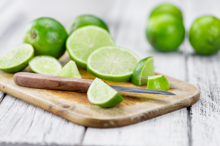 cutted: Sliced Limes on an old wooden table as detailed close-up shot (selective focus)