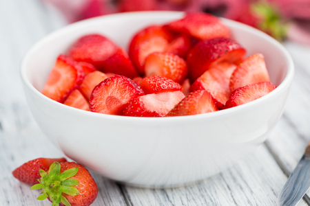 berry: Fresh made Chopped Strawberries on a vintage background as detailed close-up shot
