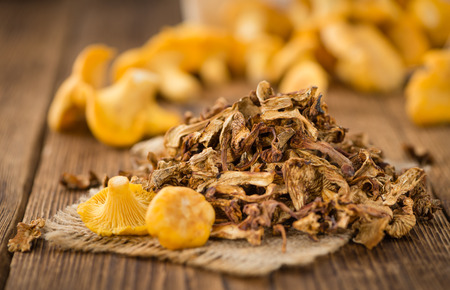 Dried Chanterelles on an old wooden table as detailed close-up shot; selective focus Stock Photo