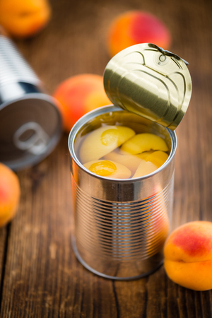 Canned Apricots on an old wooden table as detailed close-up shot (selective focus)