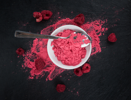 Fresh made Raspberry powder on a vintage background as detailed close-up shot